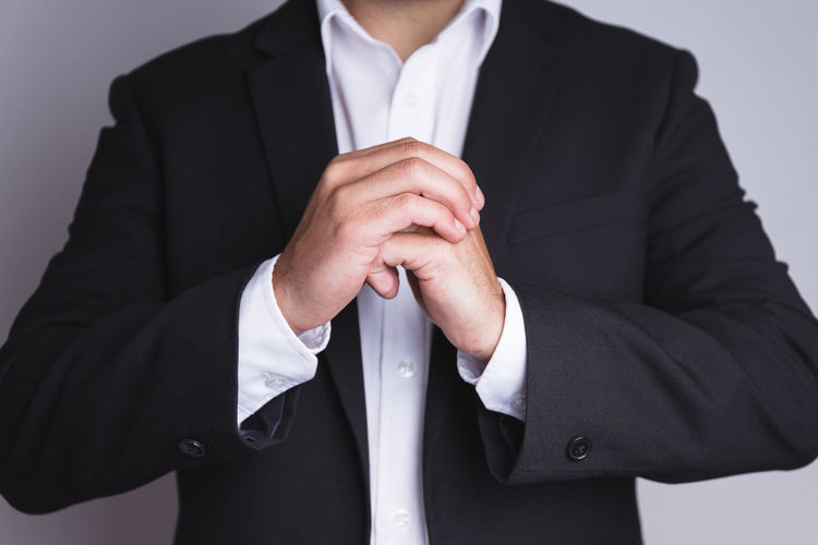 Midsection of businessman wearing black suit while gesturing