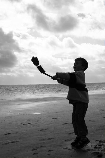 Beach Holiday One Boy Outdoors People Playing Sand Sea Silhouette Sky And Clouds Water
