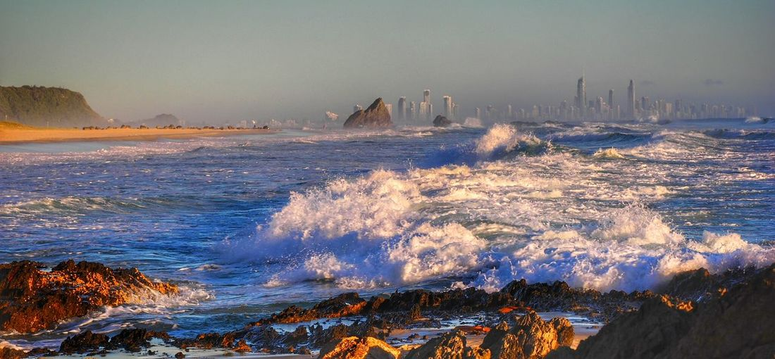 Scenic View Of Sea Waves Rushing Towards Rocky Shore