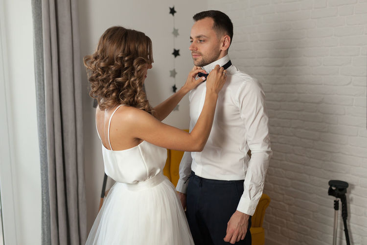 Bride adjusting bowtie of husband while standing at home
