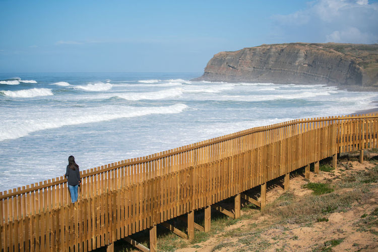 High angle view of woman looking at sea while standing on footpath