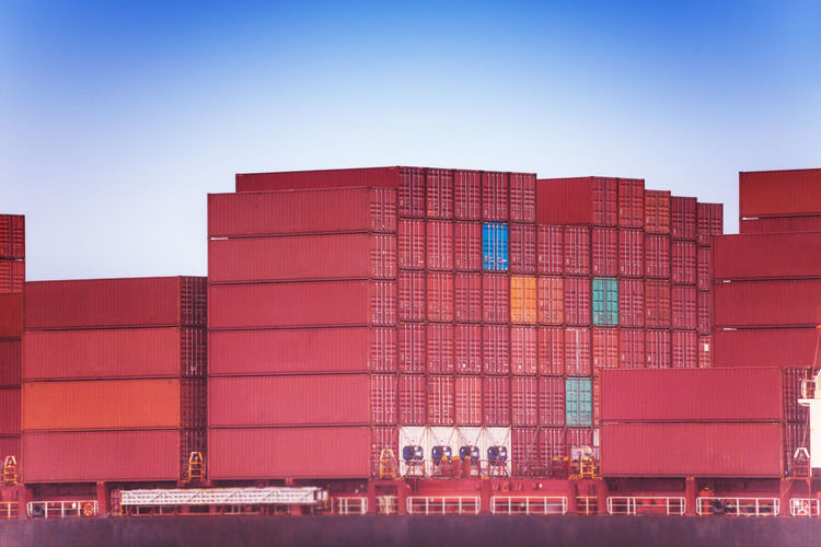View of stacked container on ship against sky