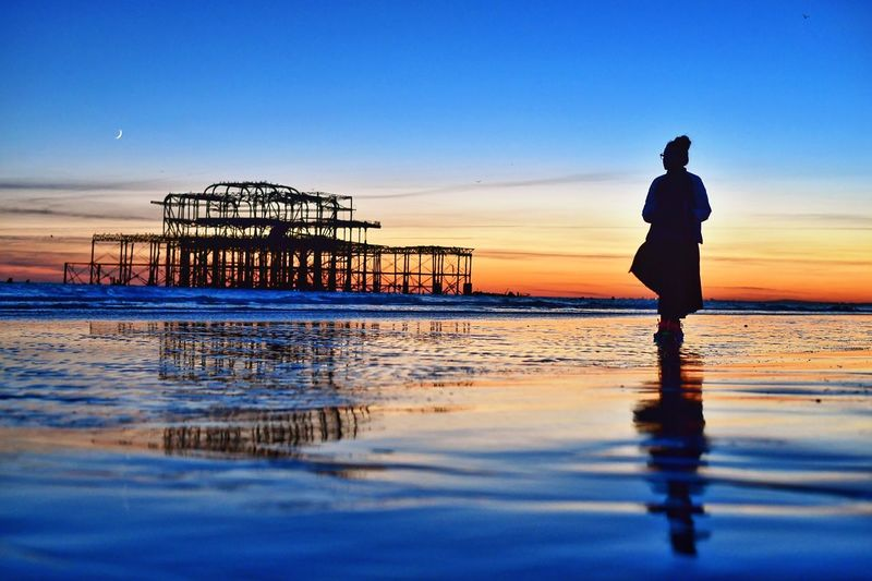 Silhouette woman standing on shore while looking at ruined west pier during sunset