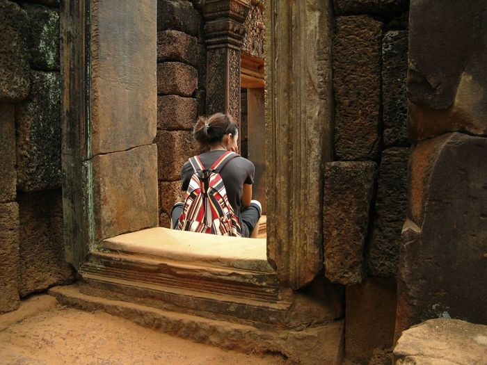Rear view of tired woman sitting at temple old ruins