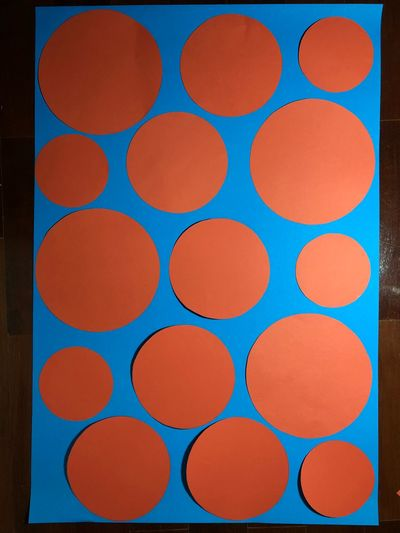 Orange colored paper in circle shaped over the blue colored paper as background. EyeEm Selects Geometric Shape Full Frame Circle Backgrounds No People Pattern Shape Multi Colored Indoors  Arrangement Repetition In A Row Blue Design Directly Above Large Group Of Objects