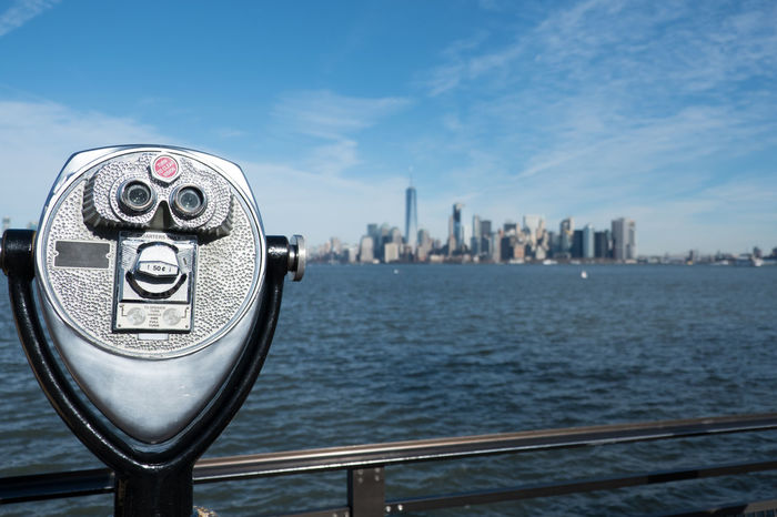 Tower viewer binoculars on a swivel stand next to a railing on the edge of Liberty Island, New York City. View of Lower Manhattan and New York Harbor from the Statue of Liberty. Bright, sunny day. Ellis Island  Hudson River Hudson River Ny Liberty Island Manhattan Manhattan New York Manhattan Skyline Manhattan, New York City New York City New York City Photos New York Harbor New York Skyline  New York ❤ New York, New York Sightseeing Statue Of Liberty Statue Of Liberty New York Tower Viewer