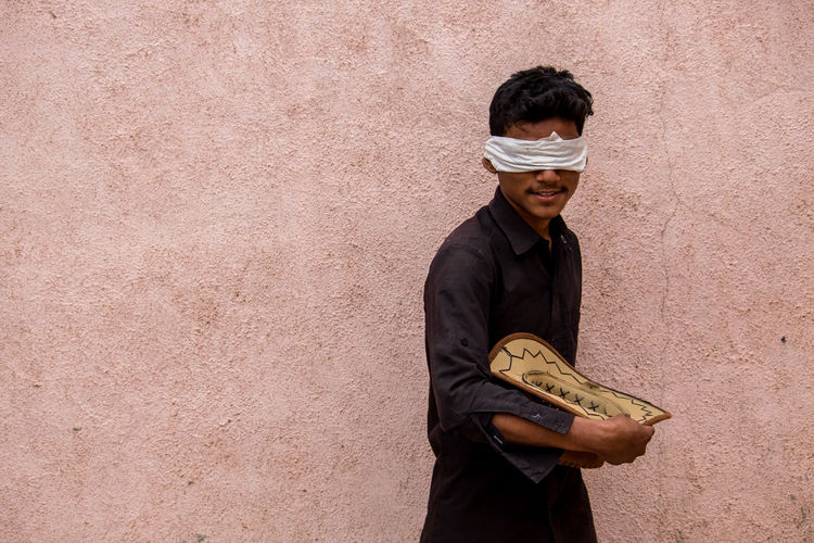 Blindfolded Boy Holding Hat While Standing Against Wall