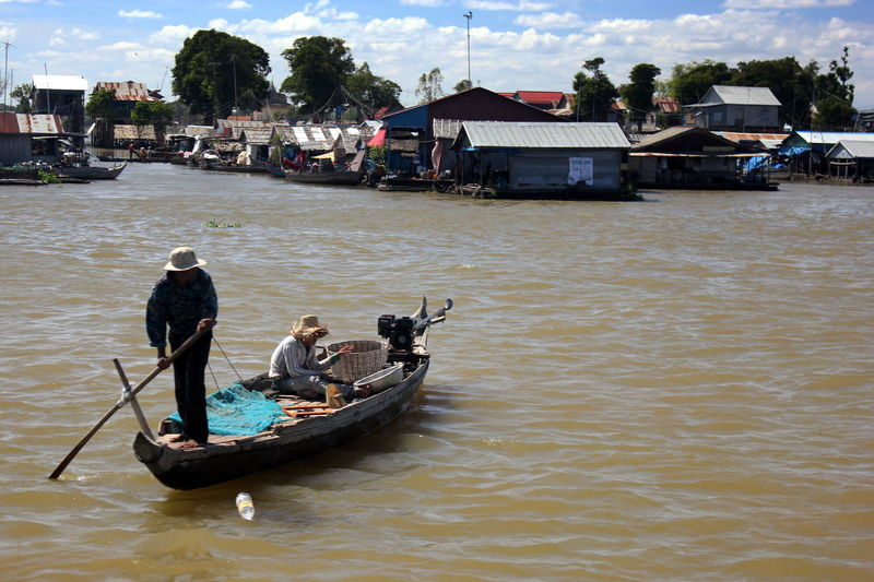 Men sailing in river by houses against sky