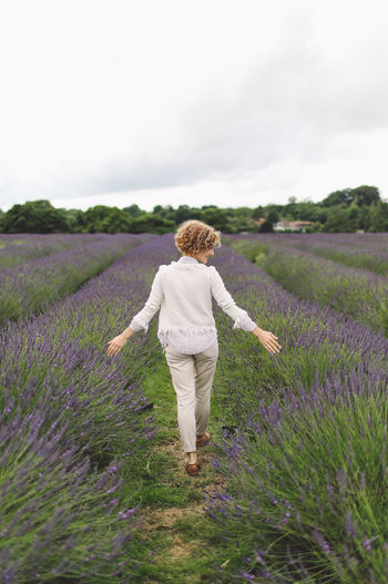 Rear View Of Woman Walking On Lavender Field Against Sky