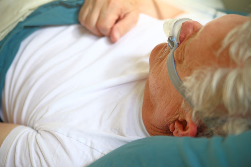 Man sleeping with cpap mask on bed at hospital