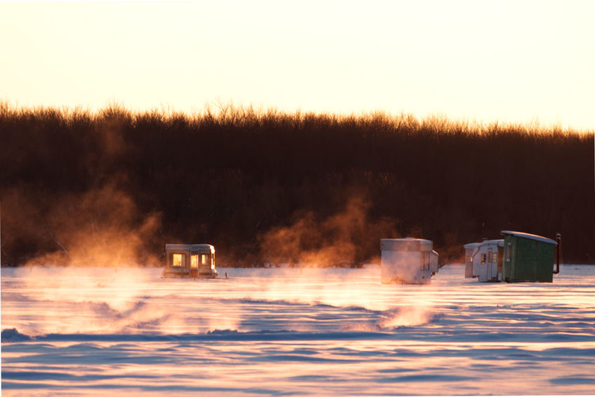 Vapor coming out of the lake where it's not completely frozen, while ice fishing huts are already installed on the lake. Frozen Lake At Sunset Frozen Lake Surface Barrel Burning Day Flame Frozen Vapor Heat - Temperature Ice Fishing Cabins Ice Fishing Huts Ice Fishing Huts On Frozen Lake At Sunset Ice Fishing Shack Nature No People Outdoors Sky