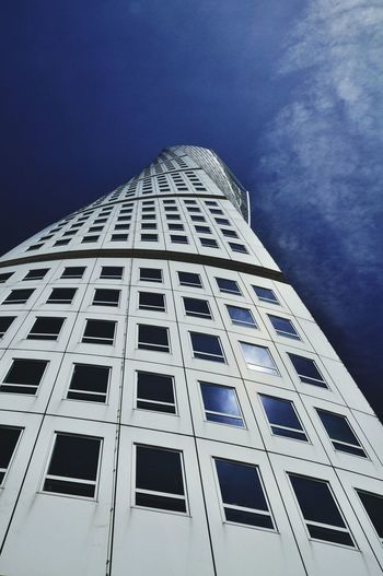 Low angle view of turning torso against sky