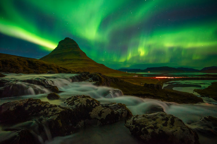 Beautiful aurora dancing over kirkjufell mountain in iceland, image noise due high iso