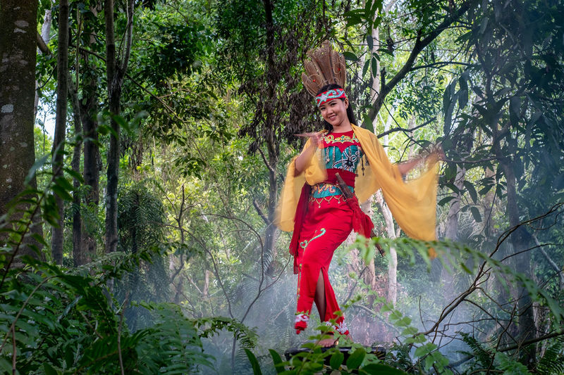 Portrait of young woman performing dance by trees in forest
