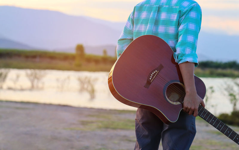 Midsection of man carrying guitar at lakeshore