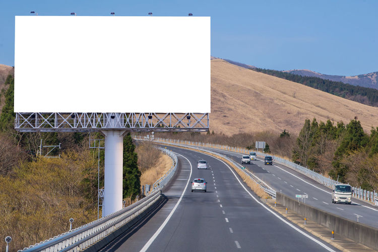 Architecture Billboard Blank Car Communication Copy Space Day Direction Dividing Line Highway Marking Motor Vehicle Nature No People Outdoors Road Road Marking Sign Sky Symbol The Way Forward Transportation