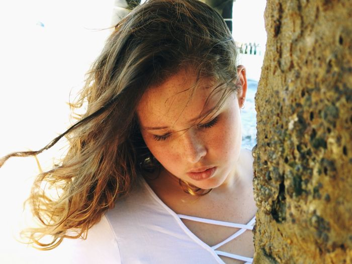 Close-up of young woman by tree