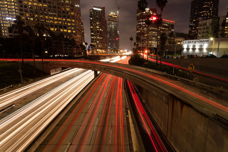 Light Trails On Bridge Over Road By Illuminated Buildings At Night