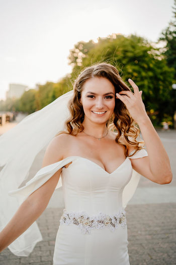 Portrait of smiling bride standing outdoors