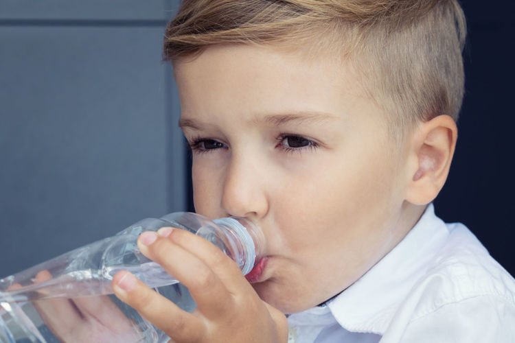 Close-up portrait of boy drinking water from glass