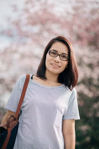 Beautiful Woman Casual Clothing Close-up Day Eyeglasses  Fashion Focus On Foreground Front View Fujifilm Leisure Activity Lifestyles One Person Outdoors Portrait Real People Smiling Standing Tabebuia Rosea Tree Trumpet Waist Up X-T20 Young Adult Young Women