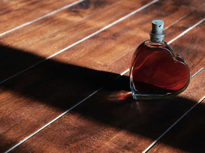 High Angle View Of Red Liquid In Heart Shape Bottle On Hardwood Floor
