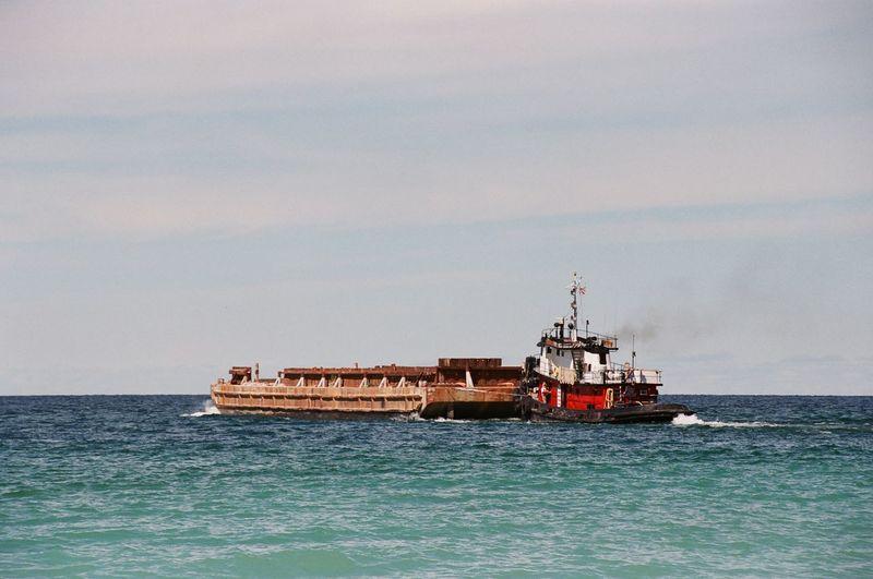 Tugboat Pushing Barge On Sea Against Sky