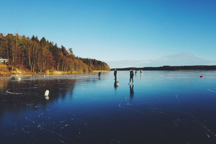 people walking and skating on ice Reflection Water Blue Lake Tree Sky Clear Sky Tranquility Outdoors Landscape Nature Day Ice Cold Temperature Winter Norway Tranquility Iceskating Wintertime Sportsman Beauty In Nature Ice Fishing Lifestyles Healthy Lifestyle Scenics The Great Outdoors - 2017 EyeEm Awards