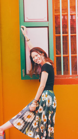 Portrait of smiling young woman standing against yellow door