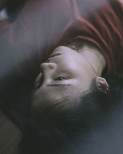 High angle view of young woman lying on bed at home