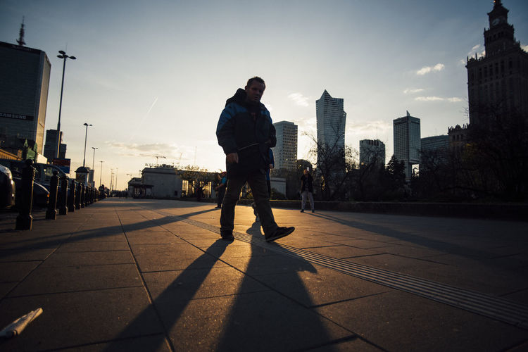 Man standing on street in city against sky during sunset