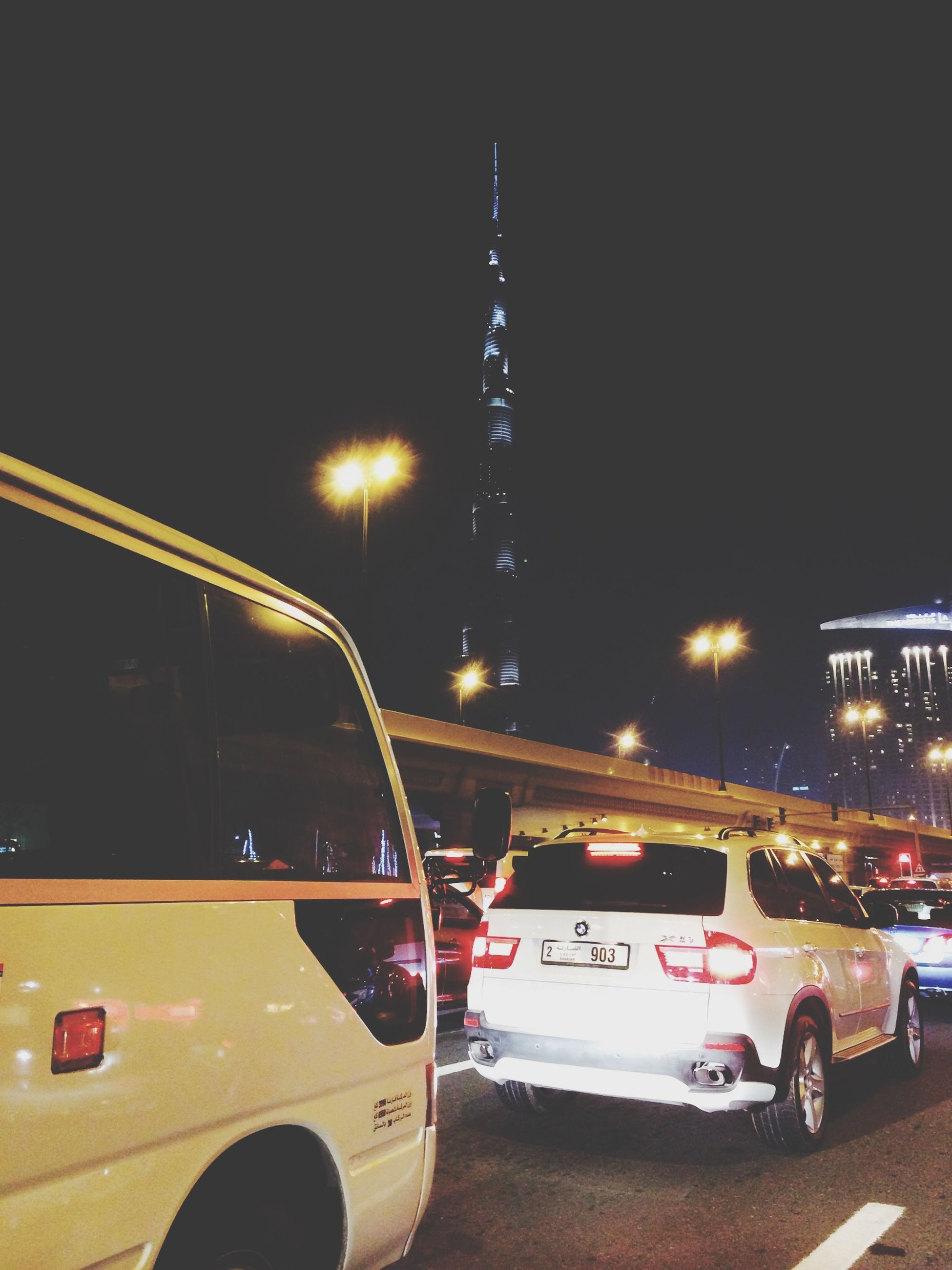 transportation, night, building exterior, architecture, illuminated, car, city, mode of transport, land vehicle, built structure, street, road, clear sky, travel, tower, traffic, tall - high, travel destinations, city life, on the move