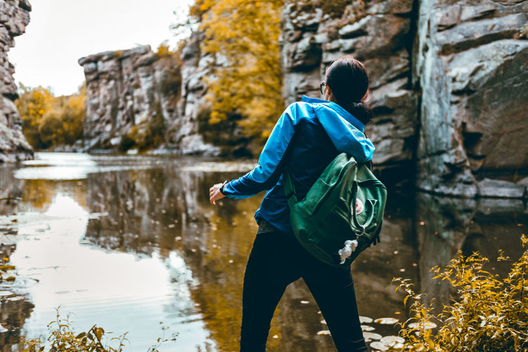 Autumn Colors Fall Colors Architecture Backpack Building Exterior Casual Clothing Day Full Length Leisure Activity Lifestyles Men Nature Outdoors People Real People Rear View Rocks And Water Standing Throwing Rocks Tree Water Women Young Adult Young Women