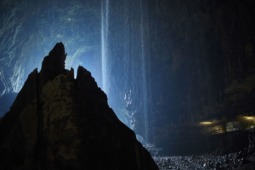 Rock formation with waterfall backlit inside the Mulu Cave Backlight Beauty In Nature Bored Cave Cliff Darkness And Light Illuminated Malaysia Moon Mysterious Nature Non-urban Scene Outdoors Power In Nature Sarawak Silhouette Tranquil Scene Travel Wanderlust Waterfall