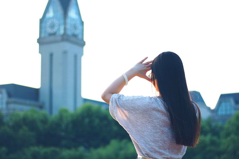 Rear View Of Woman Shielding Eyes Against Bell Tower