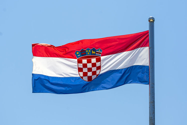 Low angle view of croatian flag waving against clear blue sky