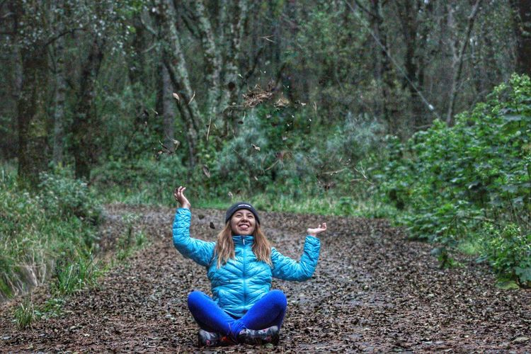 Full length of smiling woman sitting on land in forest