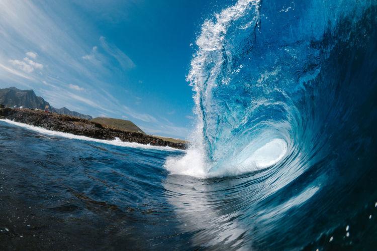 Water splashing in sea against blue sky