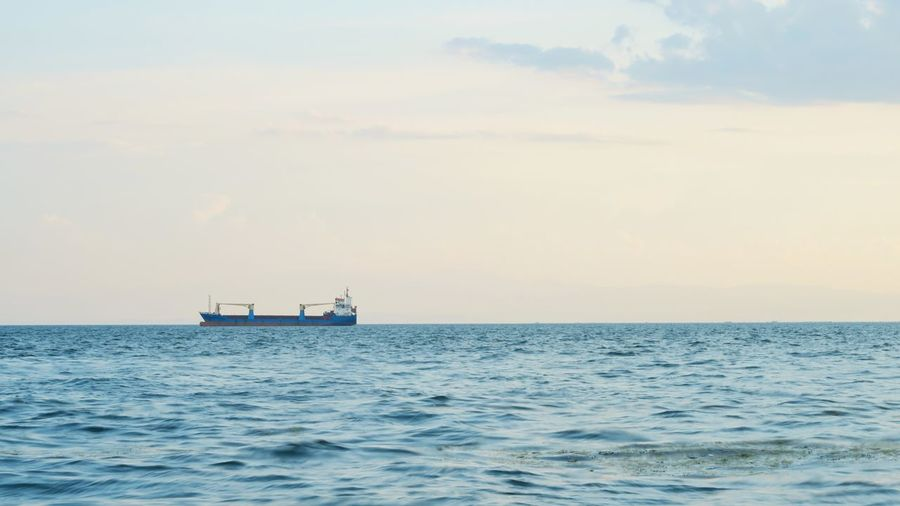 industrial cargo ship on the horizon with only water in the foreground Thessaloniki Thermaic Gulf Cargo Ship Cargoship Clean Copyspace Nautical Vessel Water Sea Sunset Sailing Beach Blue Summer Sky
