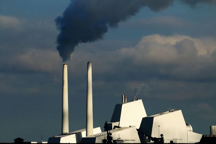 Smoke emitting from chimney against sky. poweplant in copenhagen on a windless morning.