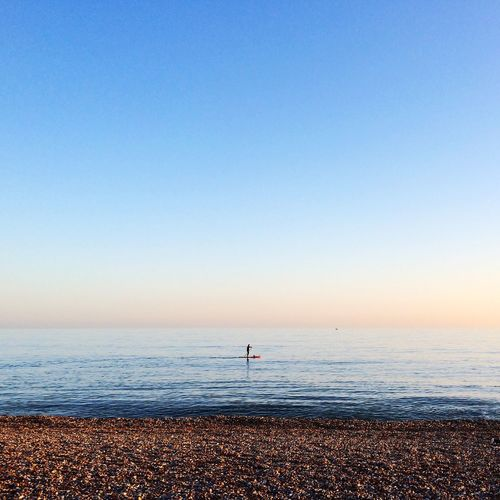 Man Paddleboarding In Sea