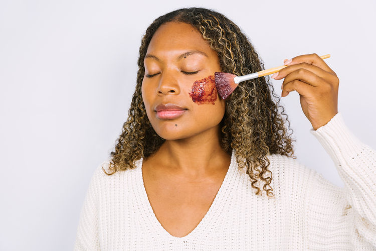 Woman applying face mask against white background