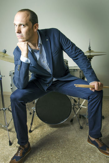 Confident drummer sitting on drum against wall