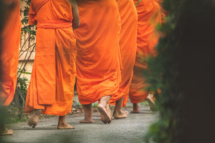 Low Section Of People Wearing Orange Traditional Clothing While Walking On Road