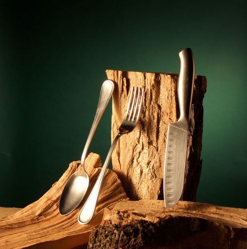 Close-up of knife and eating utensil on woods against green background