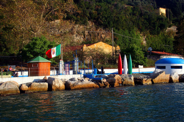 Palmaria Island with bathhouse view from the boat Bunker Italy Flag Architecture Building Exterior Built Structure Cabin Day Flag Nature Nautical Vessel No People Outdoors River Rocks Sea Sky Transportation Tree Water Waterfront