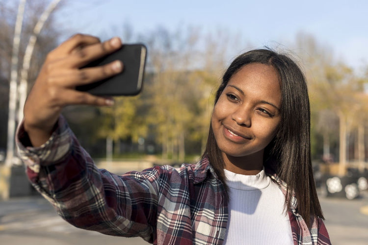 Young woman taking selfie while standing outdoors