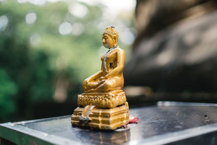 Close-up of buddha figurine on table