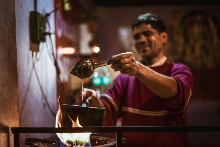 Indian man making tea in restaurant