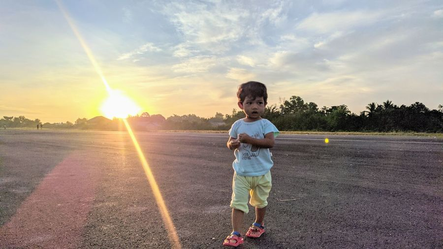 Boy standing on street against sky during sunset
